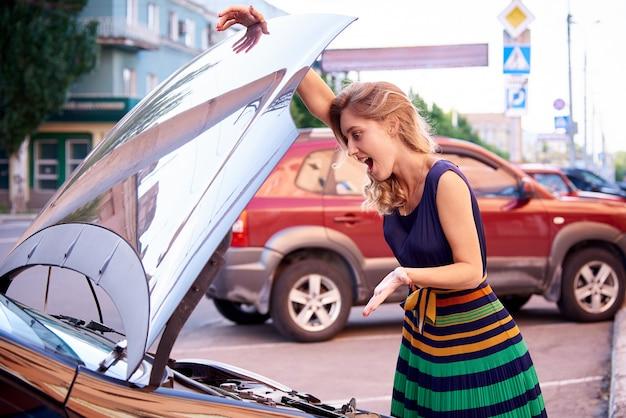 Garota perplexa perto do carro com um capô aberto.