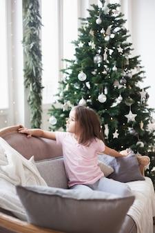 Garota perto da árvore de natal, esperando o papai noel e um milagre
