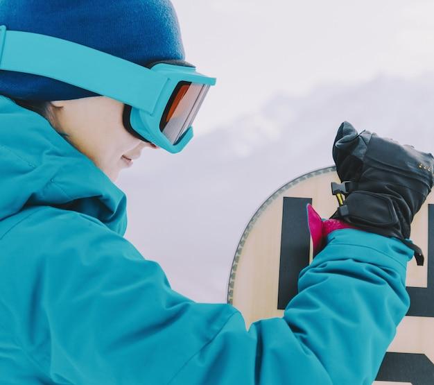 Garota piloto com snowboard no inverno