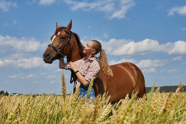 Garota piloto fica ao lado do cavalo no campo