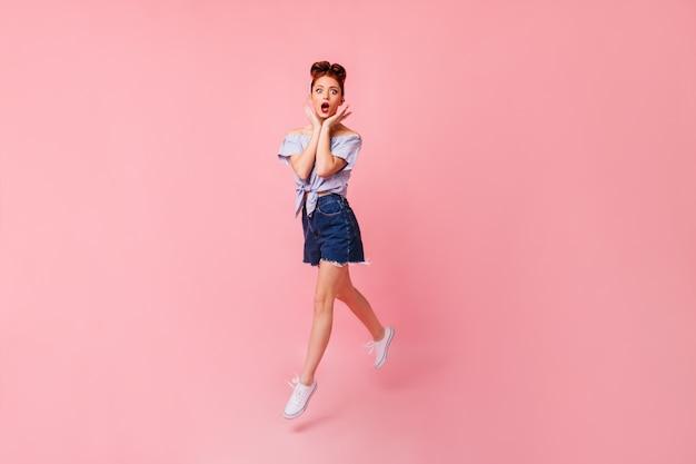 Garota pin-up chocada em sapatos brancos, posando com a boca aberta. visão de comprimento total de mulher ruiva emocional pulando no espaço rosa.