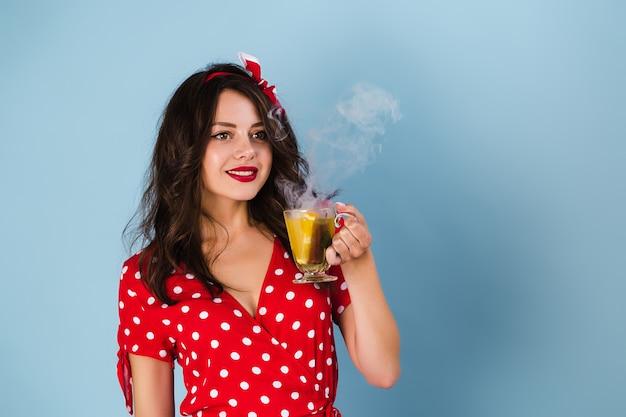 Garota pin-up em um vestido fica em um fundo azul, segurando um copo com uma bebida