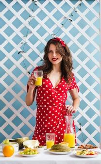 Garota pin-up em um vestido vermelho com um copo de suco de laranja nas mãos
