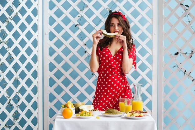 Garota pin-up em um vestido vermelho come melão