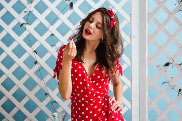 Garota pin-up em um vestido vermelho olha para um morango brilhante, segurando na mão