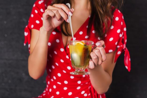 Garota pin-up, segurando um copo com uma bebida e mexendo uma colher. clouse-up