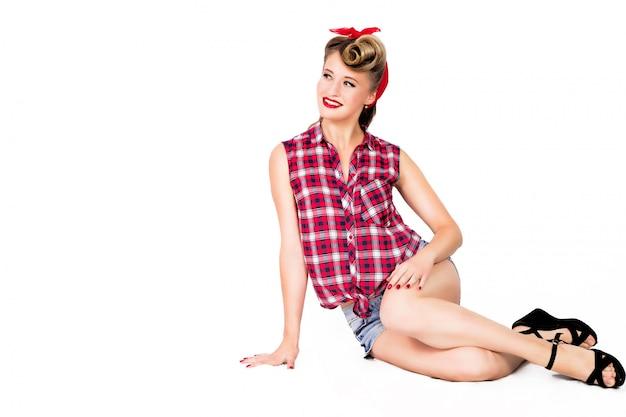 Garota pin-up sexy em shorts e sapatos de salto altos, sentado no chão, sobre fundo branco