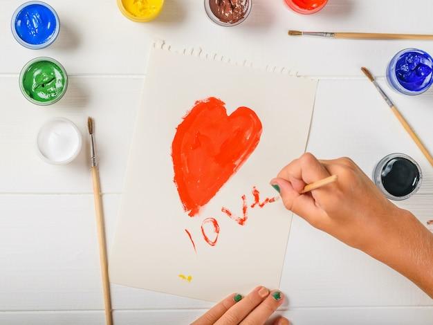 Garota pinta o coração com tinta vermelha e escreve a palavra amor.