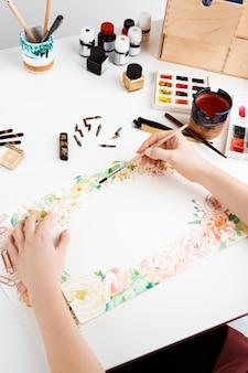 Garota pintando flores em papel com aquarela.