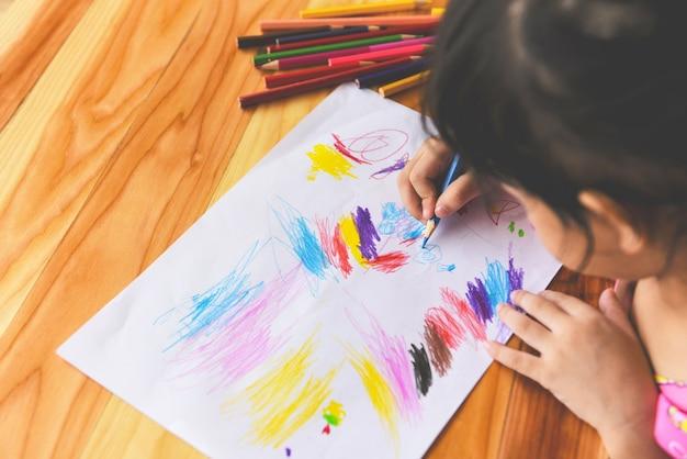Garota pintando na folha de papel com lápis de cor na mesa de madeira