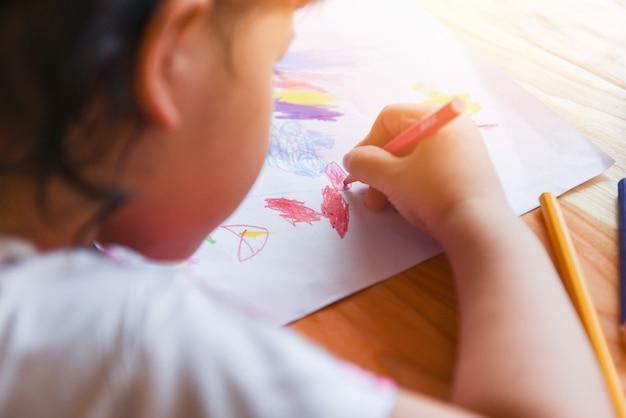 Garota pintando na folha de papel com lápis de cor sobre a mesa de madeira em casa