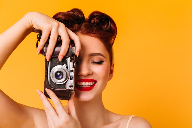 Garota pinup feliz tirando fotos. retrato de estúdio de mulher com câmera isolada no espaço amarelo.