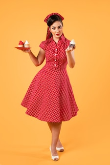 Garota pinup fofa posando com cupcakes