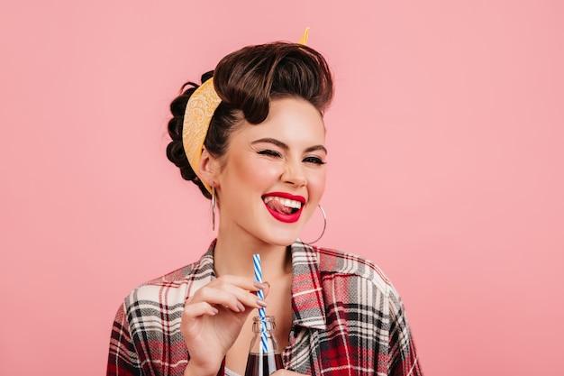 Garota pinup sonhadora com maquiagem brilhante, rindo no fundo rosa. foto de estúdio de senhora despreocupada bebendo bebida.