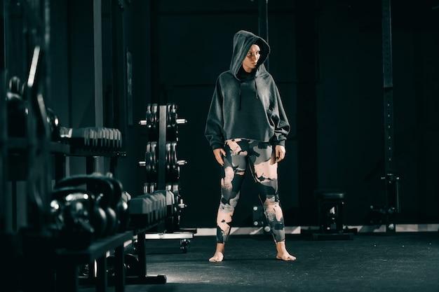 Garota poderosa boxer caucasiano posando com capuz na cabeça com os pés descalços.