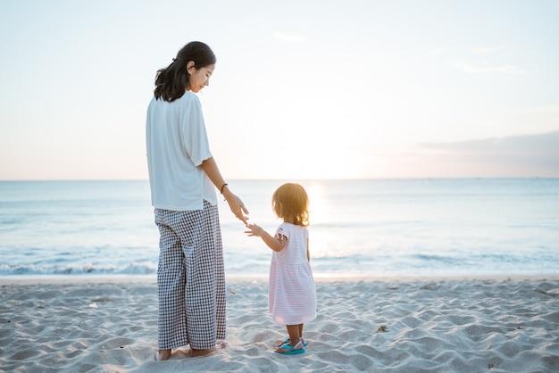 Garota por trás e um vestido branco em uma praia de verão olhando o pôr do sol