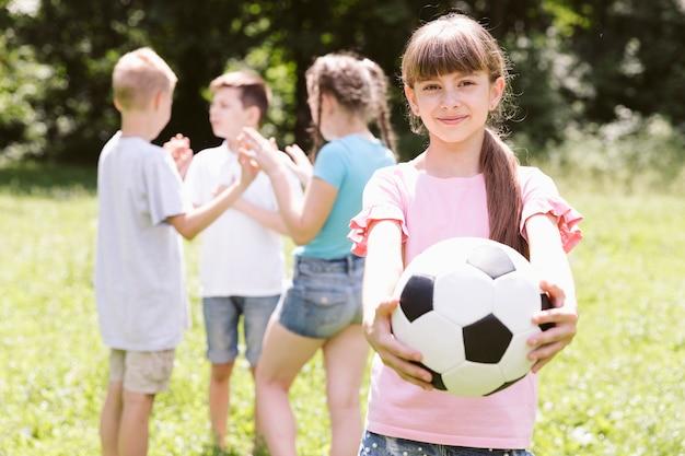 Garota posando com bola de futebol