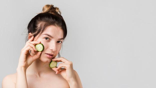 Garota posando com fatias de pepino