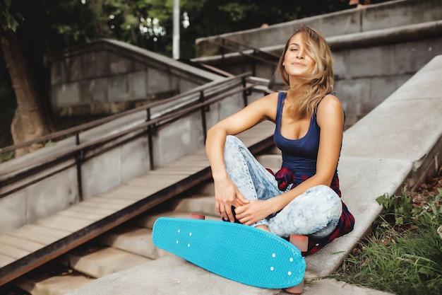 Garota posando com placa de skate