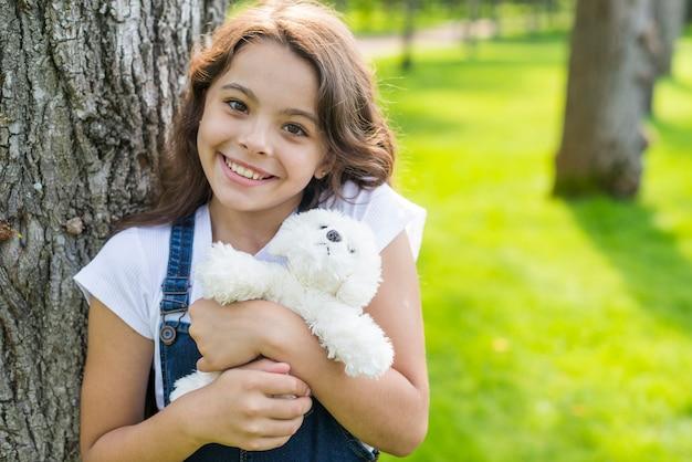 Garota posando com um brinquedo de pelúcia