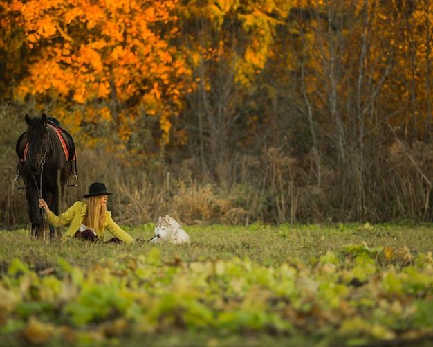 Garota posando com um cavalo e um cachorro