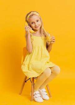 Garota posando com uma banana como telefone