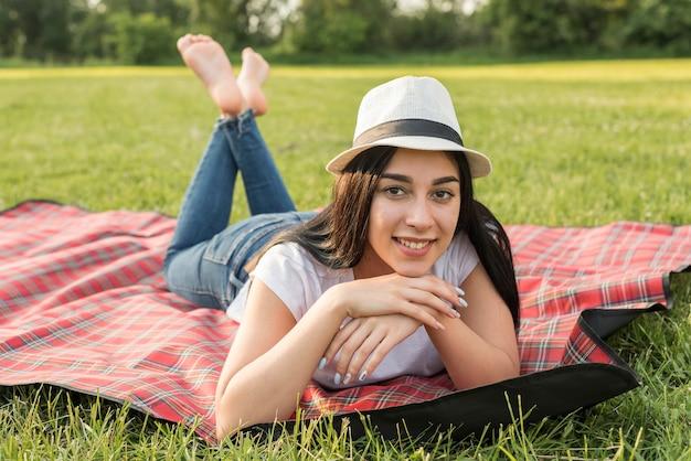 Garota posando em um cobertor de piquenique