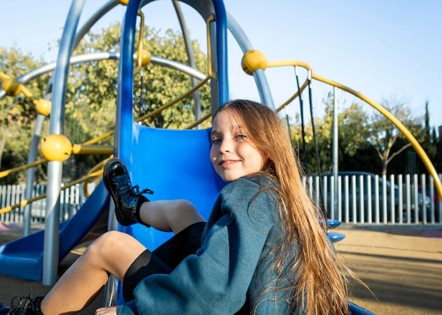 Garota posando em um slide ao ar livre