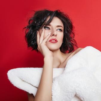 Garota posando em uma jaqueta branca sobre um fundo vermelho