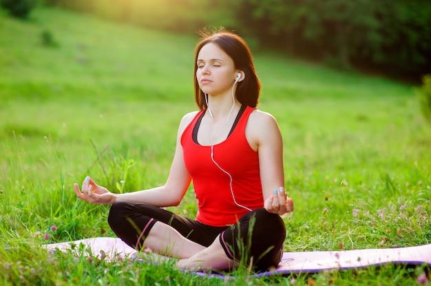 Garota posando ioga lá fora na floresta de manhã