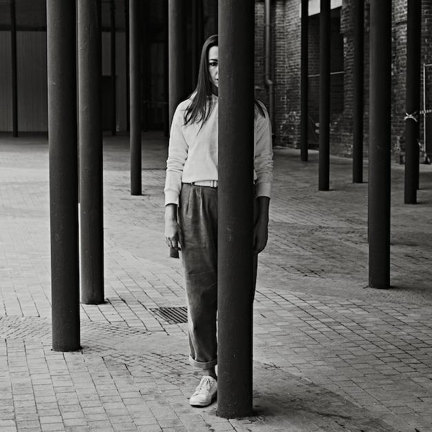 Garota posando na rua perto de colunas pretas. passeios e entretenimento na cidade.