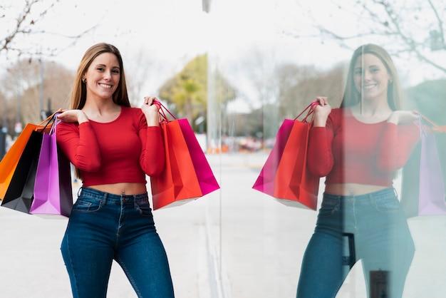 Garota posando para foto com sacos de compras