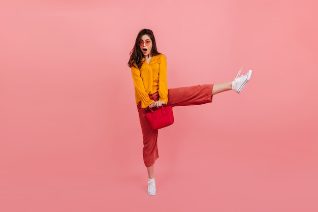 Garota positiva em roupas da moda brilhantes salta alto na parede rosa. retrato de corpo inteiro de morena surpresa com bolsa vermelha.