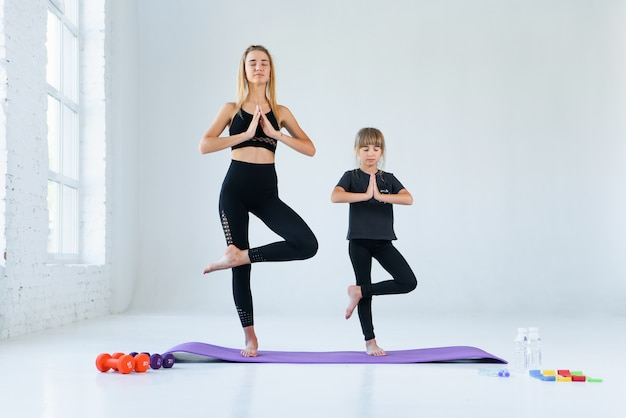 Garota praticando ioga, em pé no exercício vrksasana com namaste, pose de árvore. meditação feminina no fundo do estúdio de loft branco.