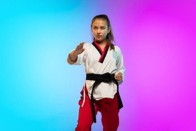 Garota praticando taekwondo com faixa preta isolada em parede gradiente