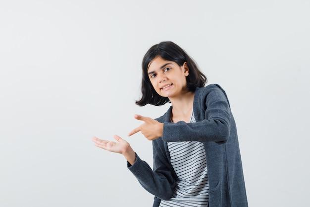 Garota pré-adolescente apontando para a mão direita na camisa, jaqueta e olhando com foco.