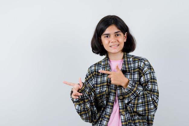 Garota pré-adolescente apontando para o lado em camisa, jaqueta e parecendo feliz, vista frontal.