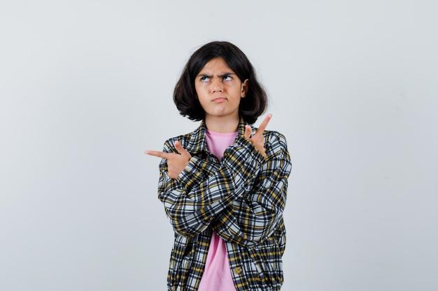 Garota pré-adolescente apontando para o verso com as mãos cruzadas na camisa, jaqueta e olhando confusa, vista frontal.