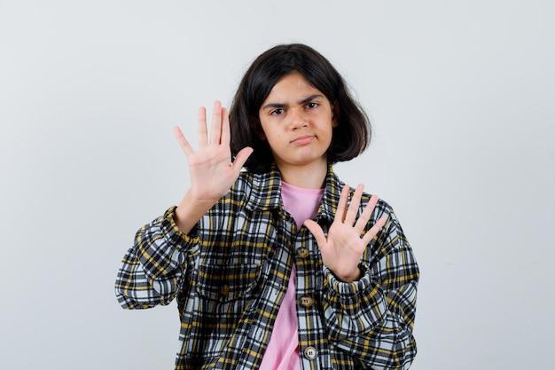 Garota pré-adolescente com camisa, jaqueta, levantando as mãos para se defender e parecendo insatisfeita, vista frontal.