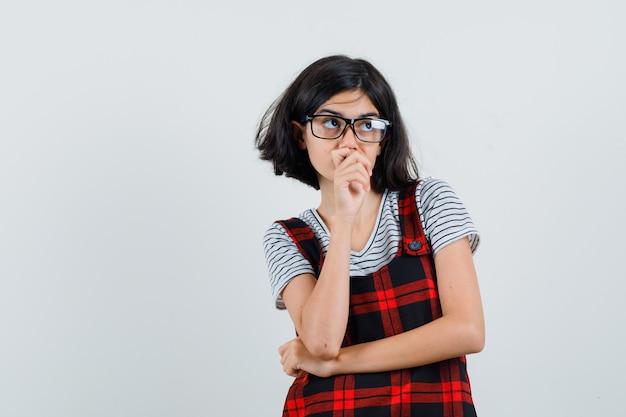 Garota pré-adolescente com camiseta, macacão e óculos pensando e parecendo pensativa
