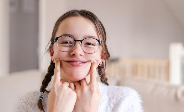 Garota pré-adolescente em copos com tranças fazendo sorriso artificial, dia de tolos de abril