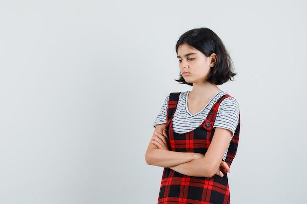Garota pré-adolescente em pé com os braços cruzados em t-shirt, macacão e olhando ofendida, vista frontal. espaço para texto
