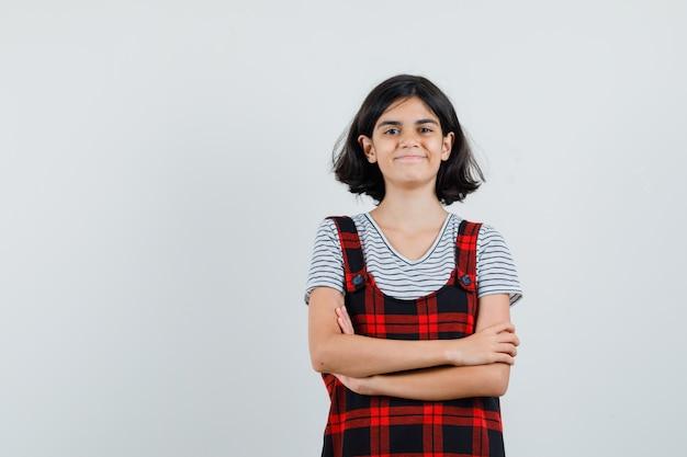 Garota pré-adolescente em pé com os braços cruzados na camiseta, macacão e parecendo esperançosa. vista frontal. espaço para texto