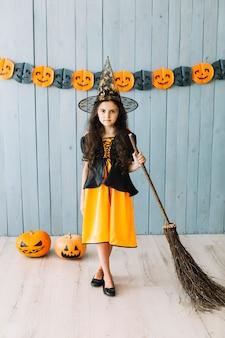 Garota pré-adolescente em pé de chapéu pontudo com vassoura