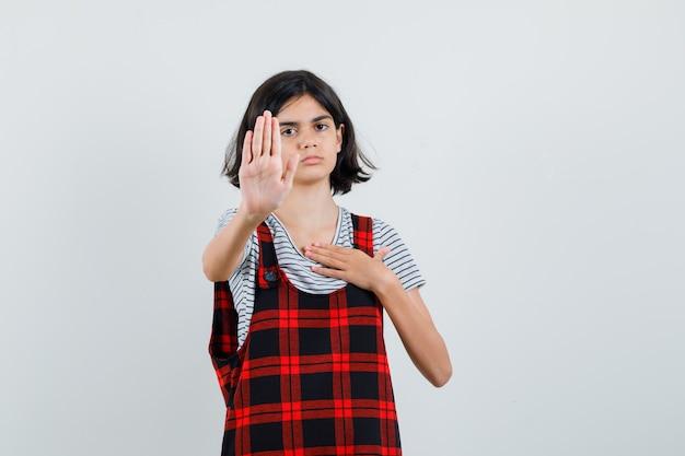 Garota pré-adolescente mostrando gesto de parada em t-shirt, macacão e parecendo desconfortável, vista frontal.