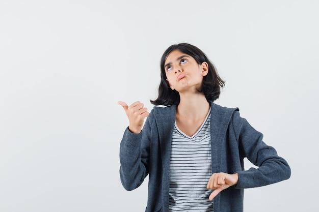 Garota pré-adolescente mostrando o polegar para cima e para baixo na camisa, jaqueta e procurando um espaço hesitante para o texto