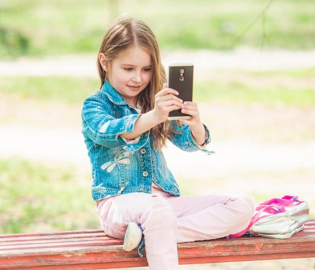 Garota pré-adolescente tirando fotos de selfie