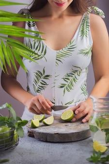 Garota prepara limonada de verão corta limão na placa