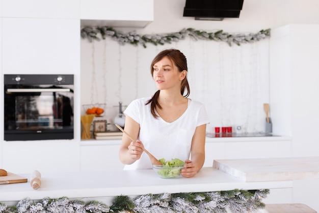 Garota preparando salada em casa na cozinha