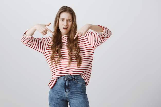 Garota presunçosa e legal apontando o dedo para baixo, exibicionista